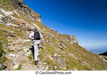 Young hiker walking to the top of charpatian mountains