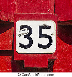 Nr. 35 - house number thirty-five on a sculptured red wall...