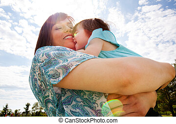 Mother and Daughter Hugging Outdoors - Happy smiling mother...