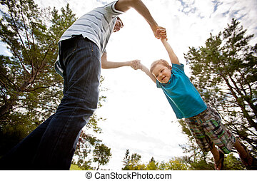 Father and Son Playing in Park - Father and son playing in...