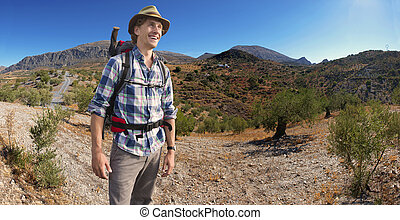 Smiling Hiker - Hiker with a backpack on his back, on a...