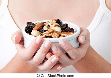 Woman Holding Bowl of Dry Fruits - Close-up of woman holding...