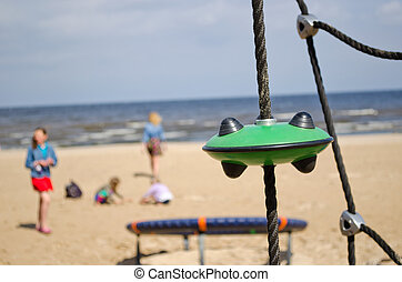 Kids in playground near sea. Climb toys equipment