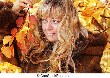 Beautiful blond middle aged woman in autumn leaves