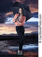 beautiful woman with umbrella, she is in front of the camera