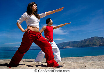 fitness on the beach - Young man and woman practice fitness...