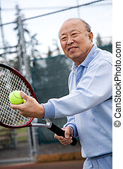 Senior tennis player - A shot of an senior asian man playing...