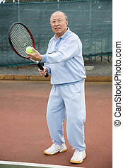 Senior tennis player - A shot of a senior asian man playing...