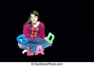 Opposites - Young woman sits in an all black room holding...