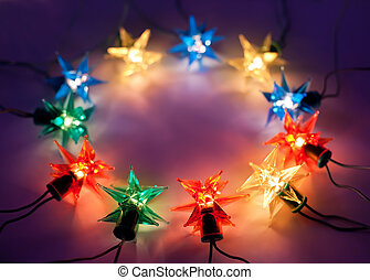 Christmas lights in ring on dark background with copy space.Decorative garland