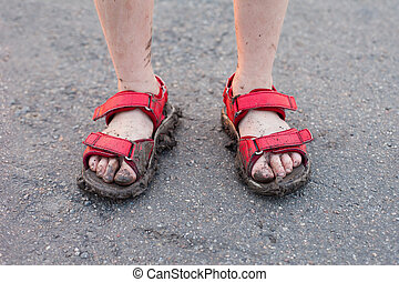 closeup of childs dirty feet in red sandals on asphalt