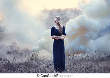 sensual beautiful girl in smoke on nature on sunset