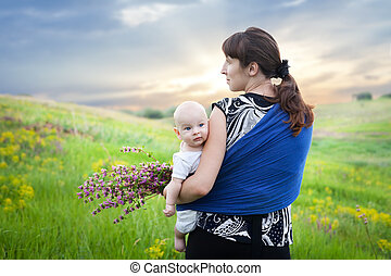 mother and baby boy in sling on green meadow collect flowers...