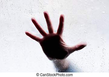 Silhouette of hand behind wet glass