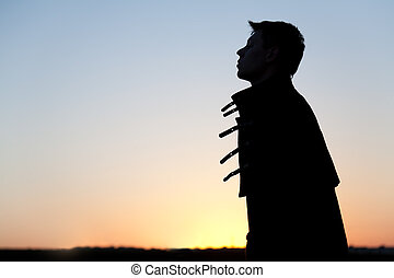 Silhouette of young man at sunset