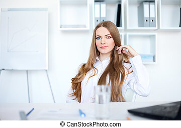 Portrait of beautiful young business woman sitting at desk...