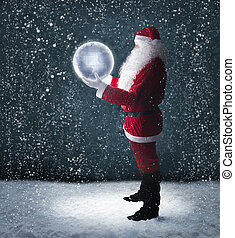 Santa Claus holding glowing planet earth under falling snow