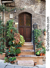 Flowers in pots on the stone steps medieval house in Assisi,