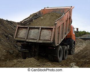 A dump truck is dumping gravel
