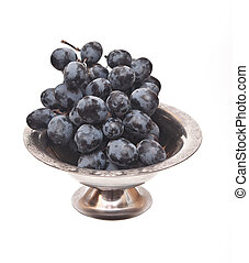 Branch of black grape in metal bowl isolated on white background.