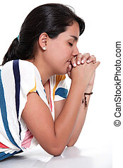 Praying - woman praying with eyes closed and hands together