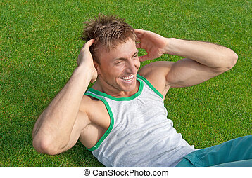 Outdoor training. Young man doing sit-ups