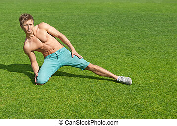Young man training on green grass - Fit young man training...