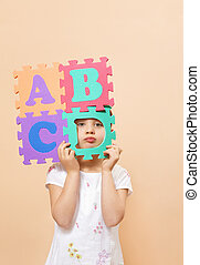 children - child learning the ABC\\\'s. The focus is on her...