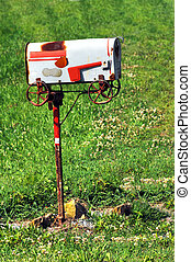 Mailbox Americana - Rustic, rural mailbox stands on grassy...