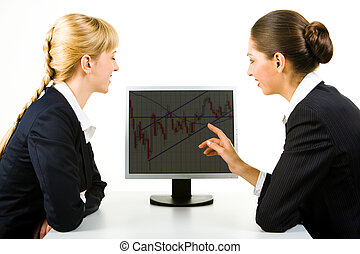 Pointing at monitor - Photo of two businesswomen sitting in...