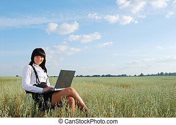 Attractive young girl working on computer in green field