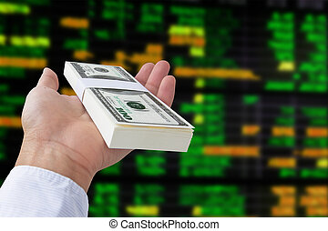 stock exchange concept - money in hand on stock exchange...