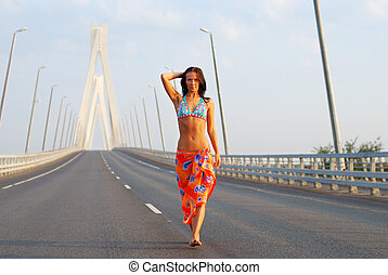 Young adult walking over  bridge