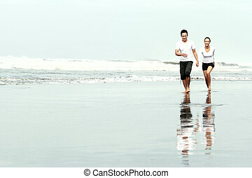 Couple running on the beach - loving couple spending quality...