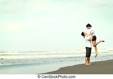 couple having fun on the beach - An attractive happy couple...