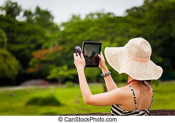 Female tourist using an iPad to take photos in Angkor Wat...