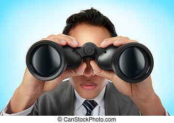 business man looking through binocular - Closeup of a young...