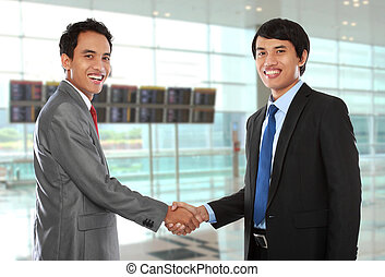 business colleagues shaking hands and smiling to the camera