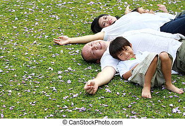Family lying down in the park - happy Family lying down in...