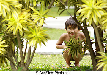 boy playing hide and seek - Portrait of happy joyful little...