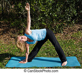 Mature Woman Yoga - Triangle Pose - Beautiful, fit woman in...