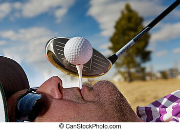 Human Golf Tee - A golfer holding a tee in his mouth