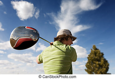 Golf driver - A golfer swinging a large wood focus on golf...