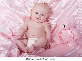Baby and bear - A baby girl on a pink blanket with a teddy...