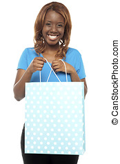 Excited woman opening the shopping bag
