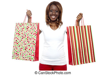Woman carrying shopping bags in both the hands