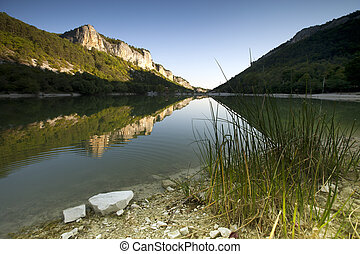 rocky and green mountains reflect by the lake