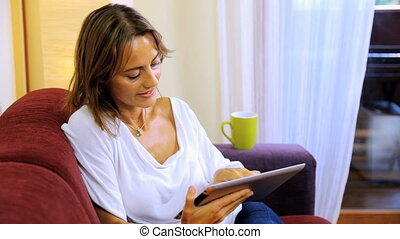 Beautiful woman reading tablet ipad - Happy woman at home...