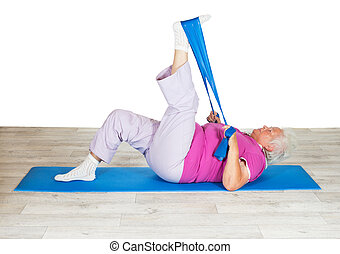 Senior woman exercising for mobility lying on a mat raising...