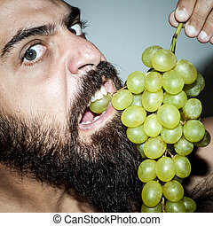 man with beard who eats voraciously grapes - terrifying man...